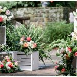 Floral Pieces on white crates in stone courtyard