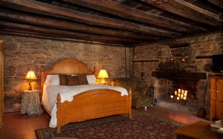 Room 11 Exposed Stone Fireplace Bedroom