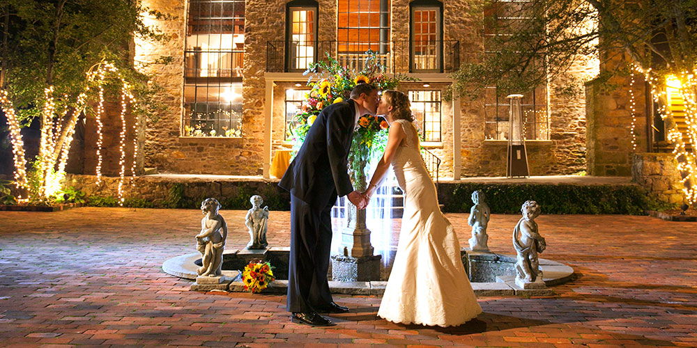 Wedding couple kissing at the HollyHedge fountain