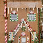 Ginger bread house with green royal icing trees bottomed with Reese cups