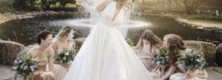 Bride in white dress in front of fountain